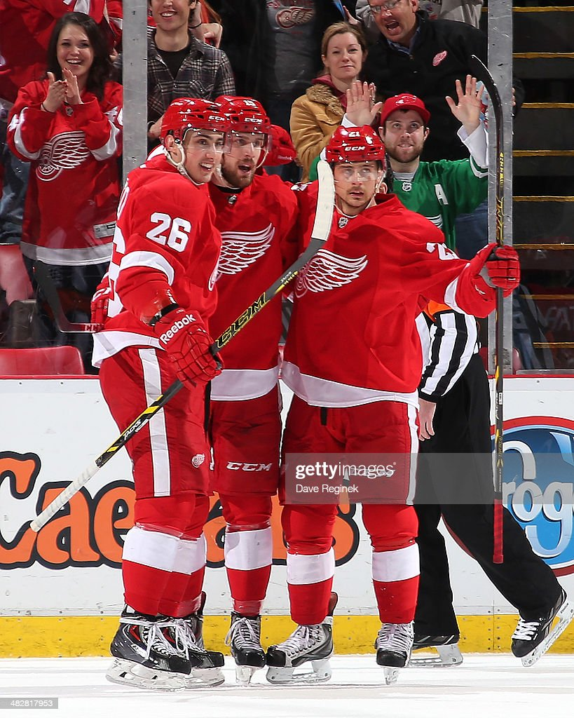 Riley Sheahan #15 and Tomas Tatar #21 of the Detroit Red Wings celebrate with teammate Tomas Jurco #26 after scoring a first period goal during an NHL game against the Buffalo Sabres on April 4, 2014 at Joe Louis Arena in Detroit, Michigan.