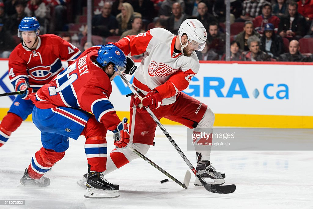 Riley Sheahan #15 of the Detroit Red Wings and Joel Hanley #71 of the Montreal Canadiens battle for the puck during the NHL game at the Bell Centre on March 29, 2016 in Montreal, Quebec, Canada. The Montreal Canadiens defeated the Detroit Red Wings 4-3.