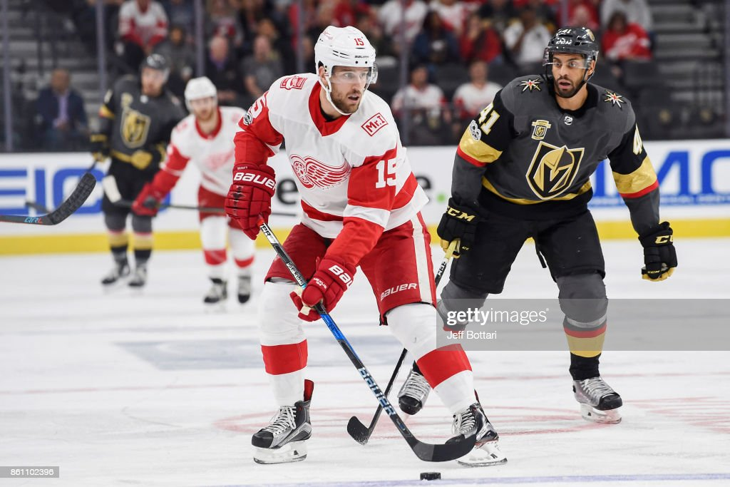 Riley Sheahan #15 of the Detroit Red Wings handles the puck with Pierre-Edouard Bellemare #41 of the Vegas Golden Knights defending during the game at T-Mobile Arena on October 13, 2017 in Las Vegas, Nevada.