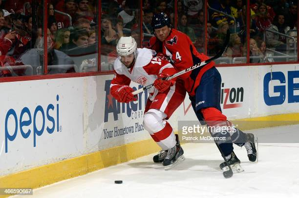 Riley Sheahan of the Detroit Red Wings is checked by John Erskine of the Washington Capitals as they battle for the puck in the first period during...