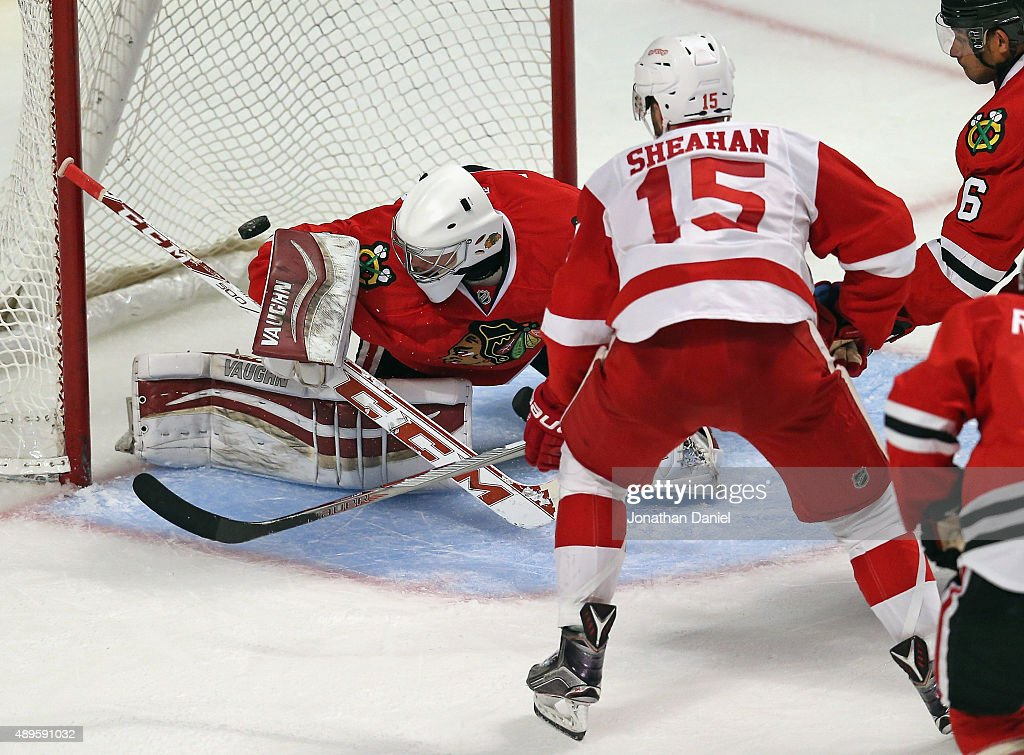 Riley Sheahan #15 of the Detroit Red Wings puts the puck over the shoulder of Mark Visentin #30 of the Chicago Blackhawks to score a goal in the 3rd period during a preseason game at the United Center on September 22, 2015 in Chicago, Illinois. The Blackhawks defeated the Red Wings 5-4 in overtime.