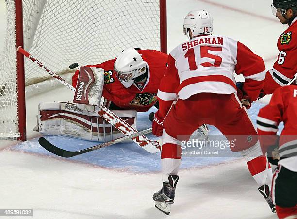 Riley Sheahan of the Detroit Red Wings puts the puck over the shoulder of Mark Visentin of the Chicago Blackhawks to score a goal in the 3rd period...