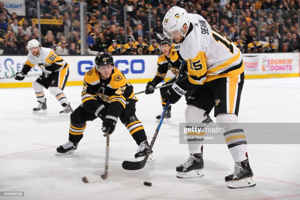 Riley Sheahan #15 of the Pittsburgh Penguins handles the puck against Torey Krug #47 of the Boston Bruins at the TD Garden on November 24, 2017 in Boston, Massachusetts.