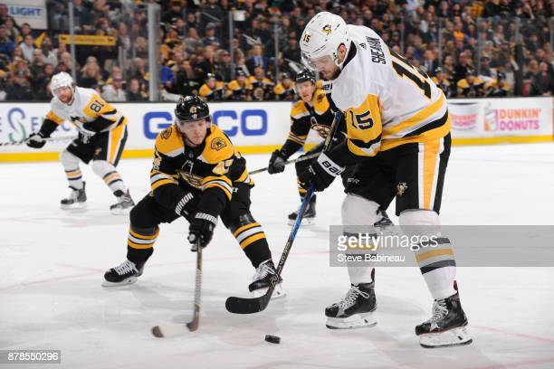 Riley Sheahan of the Pittsburgh Penguins handles the puck against Torey Krug of the Boston Bruins at the TD Garden on November 24 2017 in Boston...