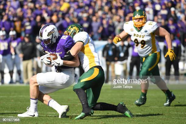 Riley Stapleton is tackled by Derrek Tuszka of North Dakota State University of James Madison University during the Division I FCS Football...