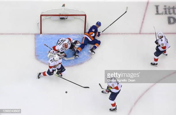 Riley Stillman of the Florida Panthers goes for the shot block as Tom Kuhnhackl of the New York Islanders falls in the crease next to goaltender...