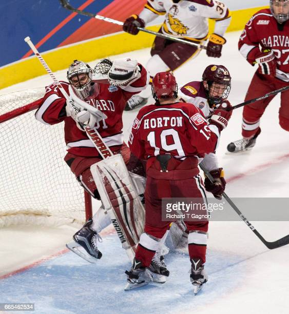 Riley Tufte of the Minnesota Duluth Bulldogs bumps into Merrick Madsen and Jake Horton both of the Harvard Crimson during game one of the 2017 NCAA...
