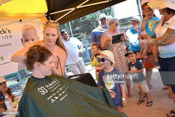 Riley Wade watches Melissa Joan Hart shave Jennifer Wade's head at the MaxLove LoomAThon 2 with Melissa Joan Hart on September 14 2014 in Tustin...