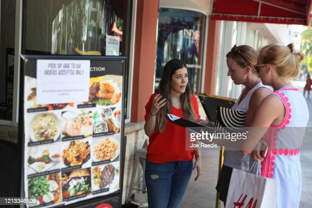 Rima Bou goes over the take out menu with Lisa Ellegard and her daughter Madeleine Ellegard at the 7 Spices restaurant along the Lincoln Road mall as...