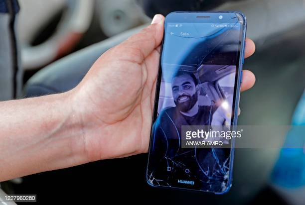 Rima Zahed shows a picture of her missing brother Mohammed, a port employee, as she waits for news at the entrance of the ravaged Beirut port, on...