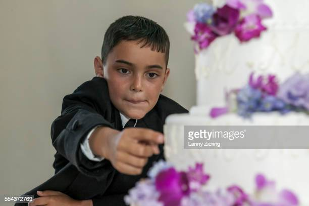 Ring bearer sneaking frosting from wedding cake