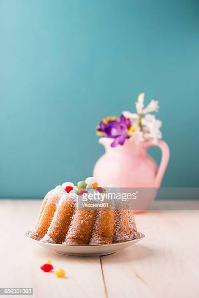 Ring cake with Easter eggs and bunch of flowers in the background