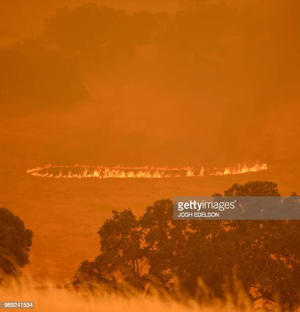 A ring of fire started by embers expands before passing through a property as the County Fire burns in Guinda California on July 1 2018 Californian...