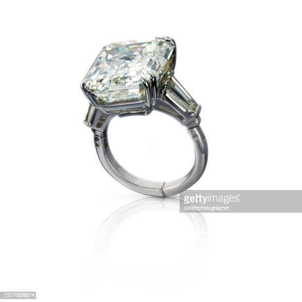 ring with a diamond leaning on a white surface - white gold stock pictures, royalty-free photos & images