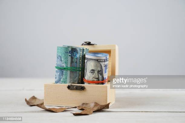 ringgit and dollar in treasure box - malaysian ringgit stock photos and pictures