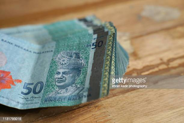50 ringgit malaysia on wooden table. - malaysian ringgit stock photos and pictures