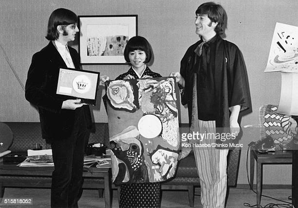 Ringo Starr and John Lennon of the Beatles with Japanese music journalist Rumi Hoshika hold up Â'Image of A WomanÂ' painted by The Beatles at Tokyo...
