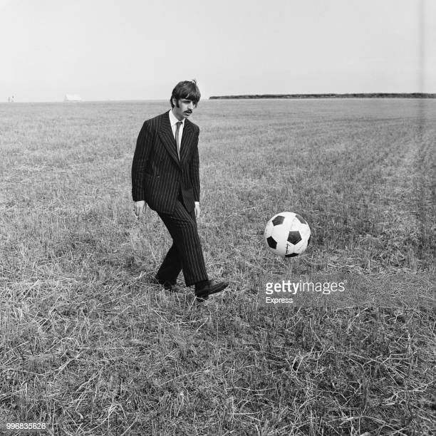 Ringo Starr, drummer with the Beatles, pictured kicking a football during filming of 'Magical Mystery Tour' in a field near Newquay in Cornwall on...