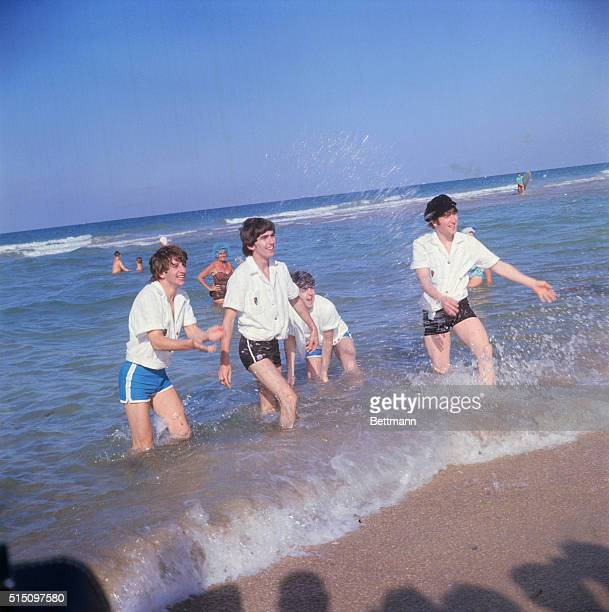 Ringo Starr George Harrison Paul McCartney and John Lennon splash onlookers while wading along the surf in Miami Beach Florida The Fab Four are in...