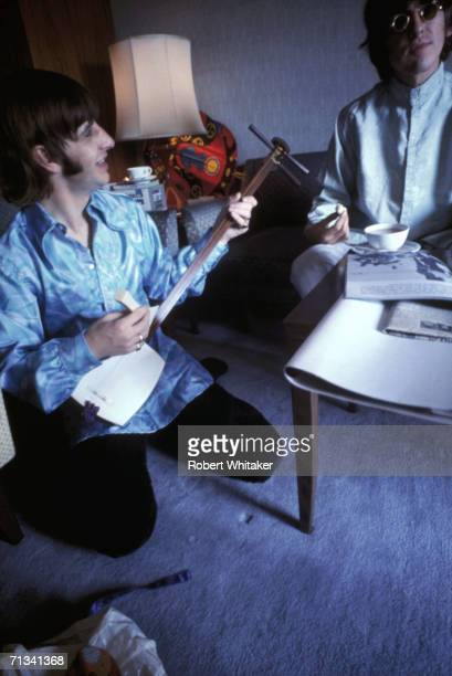 Ringo Starr plays a traditional Japanese instrument while George Harrison looks on at the Tokyo Hilton during the band's tour of Asia 1966