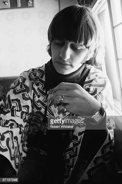 Ringo Starr plays cards on board a Japan Airlines plane from Anchorage to Tokyo at the start of the Beatles' Asian tour 28th June 1966 He is wearing...