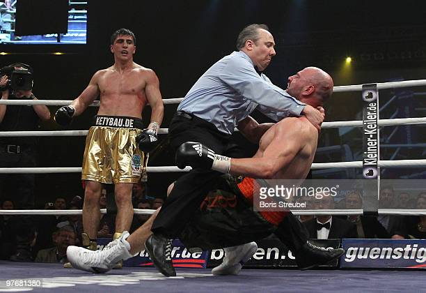 Ringreferee Marc Nelson tries to hold Adam Richards of the U.S., who falls to on the ring floor after he was knocked out by Marco Huck of Germany...