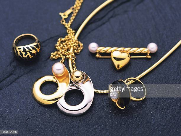 Rings, brooch, and necklaces with pearls, high angle view, black background