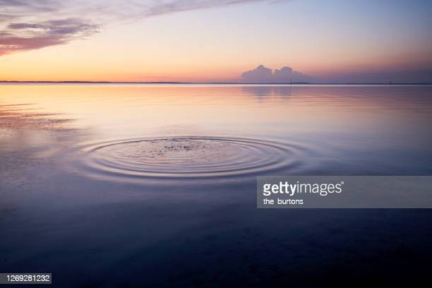 rings in water of the sea and reflection of the sky during sunset - wellness stock pictures, royalty-free photos & images