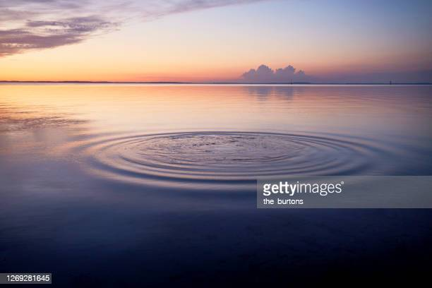 rings in water of the sea and reflection of the sky during sunset - idyllic stock pictures, royalty-free photos & images