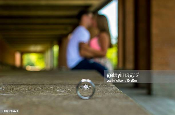 Rings On Retaining Wall Against Couple Kissing