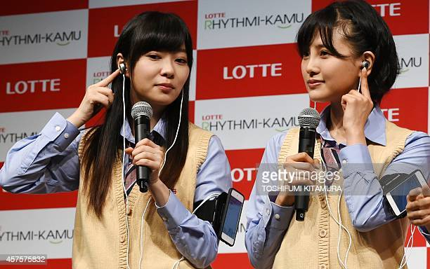 Rino Sashihara and Haruka Kodama members of HKT48 a girls pop group display Lotte's prototype 'RhythmiKamu' ear phones that count and record the...