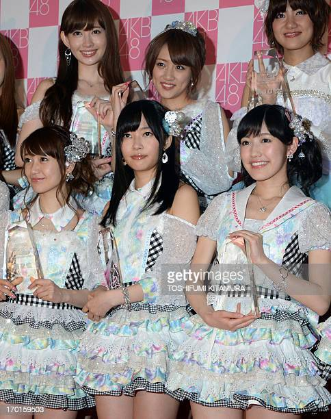 Rino Sashihara of HKT48 one part of Japanese girl pop group AKB48 poses with other selected recording members in a photo session after the group's...