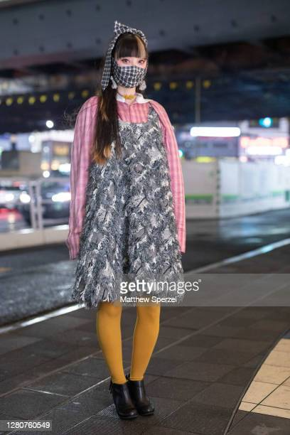 Rinrin is seen on the street wearing Perminute shirt and dress, plaid print face mask and hair tie, yellow leggings and black shoes during the...