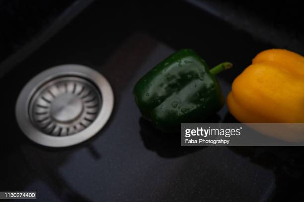 rinsing peppers in sink - das leben zu hause stock pictures, royalty-free photos & images