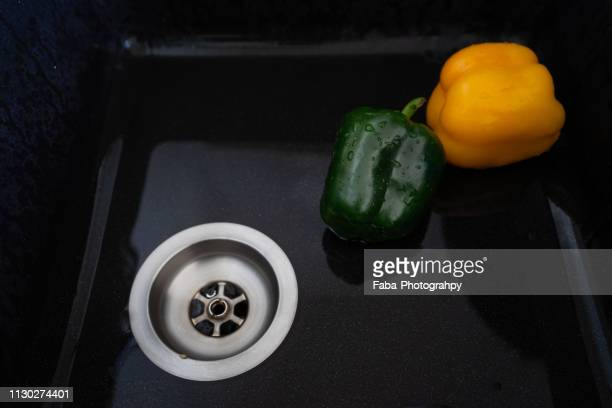 rinsing peppers in sink - gesunder lebensstil stock pictures, royalty-free photos & images