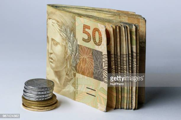 In this image Brazilian coins of 1 Real and 50 cents along with 50 Real Bank notes Image showing Brazilian bills and coins In Brazil the official...