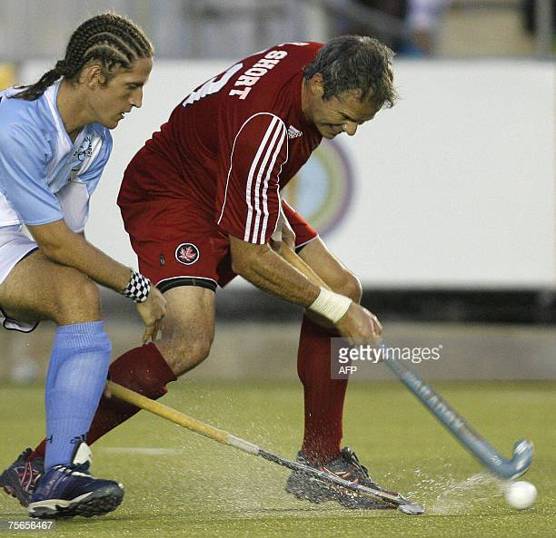 Rob Short of Canada dribbles the ball under pressure of Argentinian Tomas Argento during their field hockey Gold medal match at the XV Pan American...