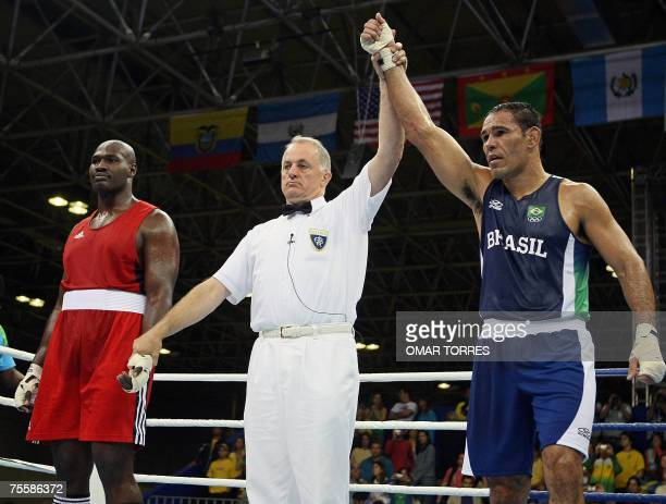 The referee raises the arm of Antonio Nogueira of Brazil at the end of the Superheavyweight preliminary round fight against Enoch Romeo of...