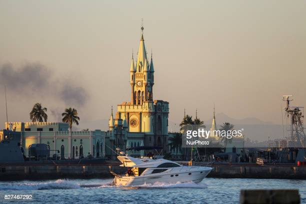 Rio de Janeiro has sunny and hot afternoon in winter In this image speedboat sails in front of historic building of the Fiscal Island during sunset...