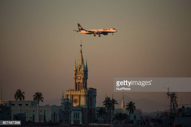 Rio de Janeiro has sunny and hot afternoon in winter In this image Azul's airplane overhead fleets historic building from Fiscal Island during sunset...