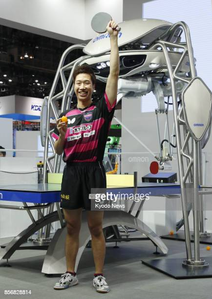 Rio de Janeiro Olympics bronze medalist Jun Mizutani poses after playing table tennis with a robot called Forpheus at the venue of the CEATEC Japan...