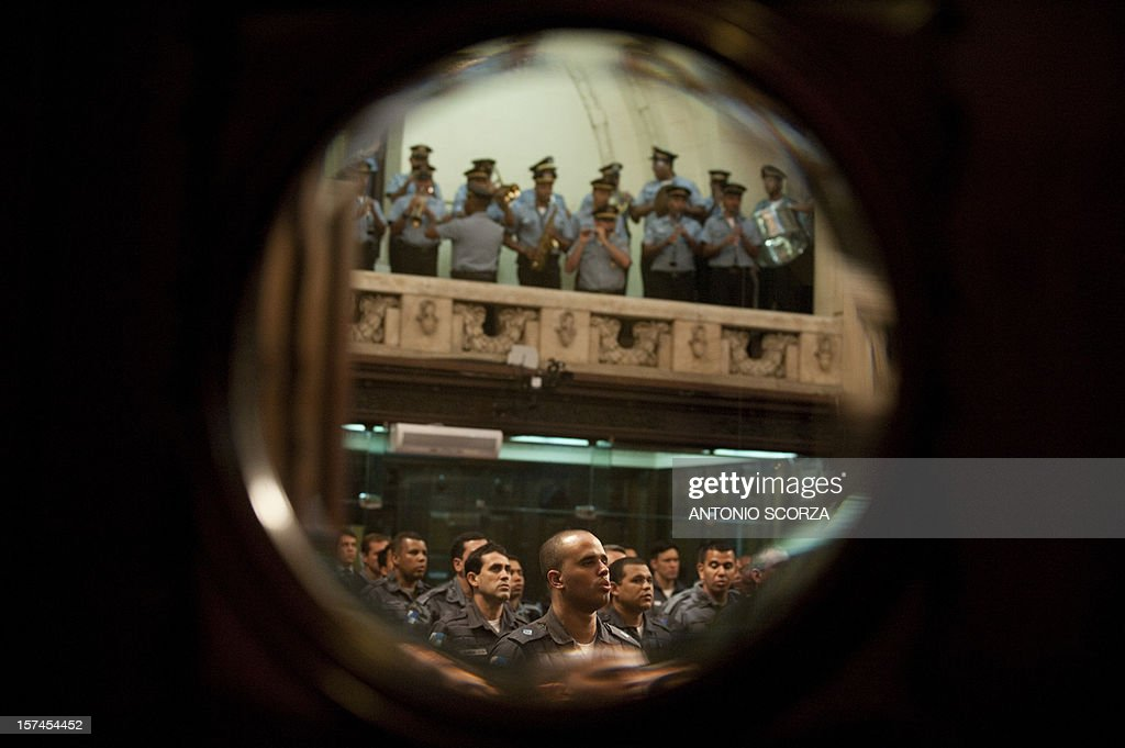 Rio de Janeiro paramilitary police personnel sing the national anthem at Rio de Janeiro's deputies plenary assembly on December 3, 2012 during a ceremony to present a citizens' initiative to increase the penalties for crimes committed against policemen.
