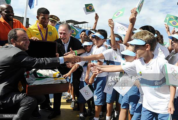 Rio de Janeiro state governor Sergio Cabral and Brazilian Olympic Committee president Carlos Arthur Nuzman show the Olympic flag to children and...