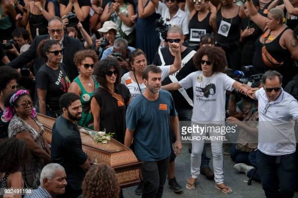 Rio de Janeiro's councilman for the leftwing party PSOL David Miranda and state congressman Marcelo Freixo of the same party carry the coffin of...