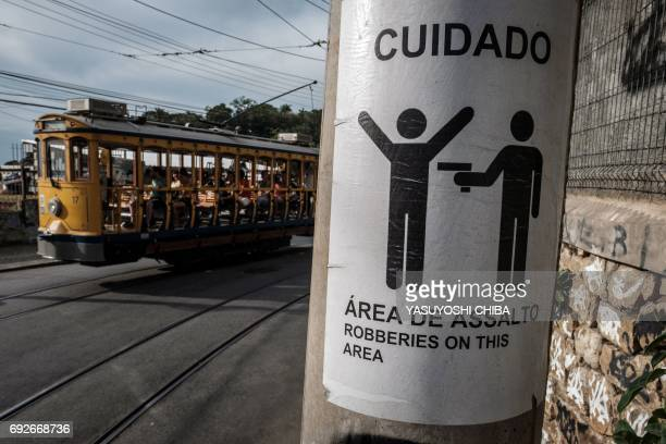 TOPSHOT Rio de Janeiro's famous street car passes by a sign warning against robberies on an electricity pole in the Santa Teresa district where local...