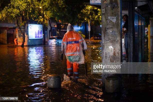 A Rio de Janeiro's street cleaner walks in the water at Voluntarios da Patria street Botafogo neighborhood while a woman protect herself inside the...