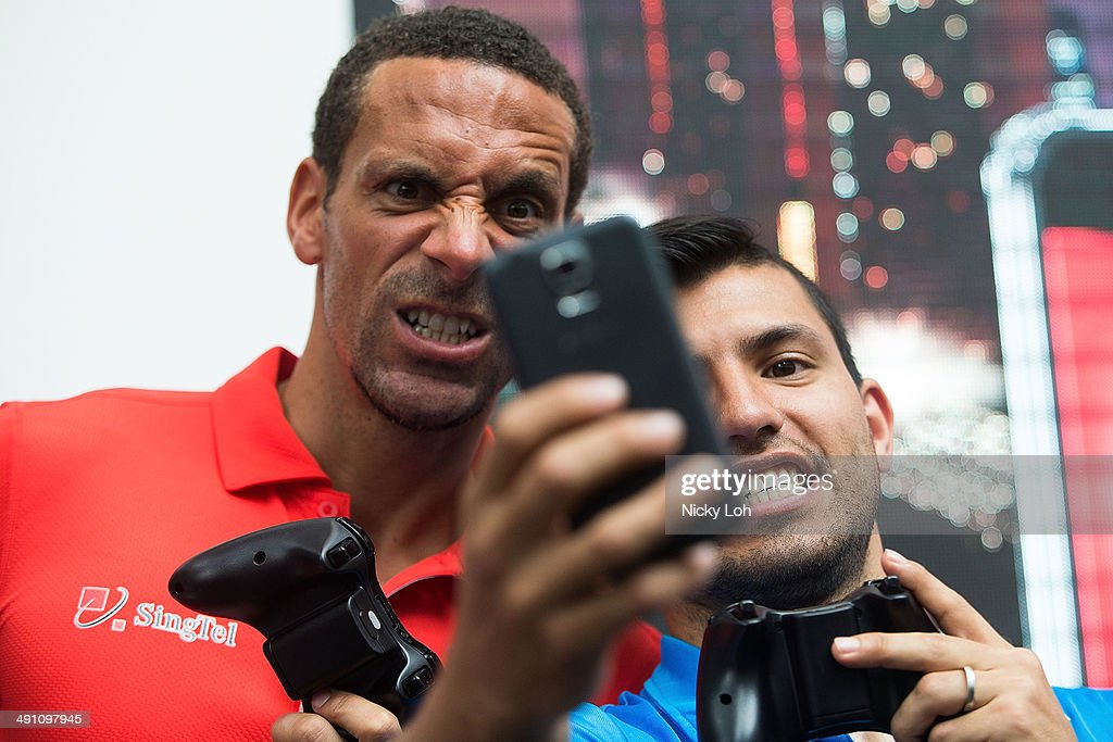 Rio Ferdinand and Sergio Aguero of Manchester City take a 'selfie' during a meet-the-fans session on May 16, 2014 in Singapore.