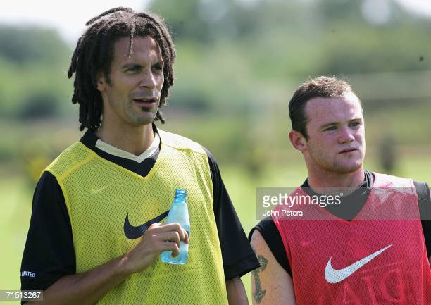 Rio Ferdinand and Wayne Rooney of Manchester United take a break from training during a first team training session at Carrington Training Ground on...
