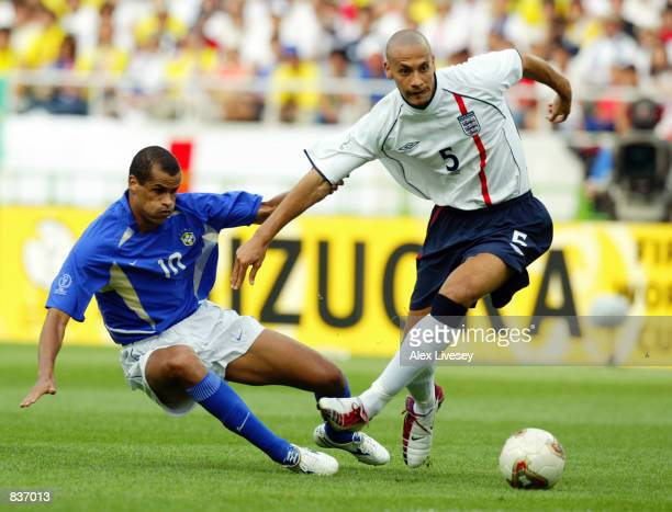 Rio Ferdinand of England takes the ball past Rivaldo of Brazil during the FIFA World Cup Finals 2002 Quarter Finals match played at the Shizuoka...