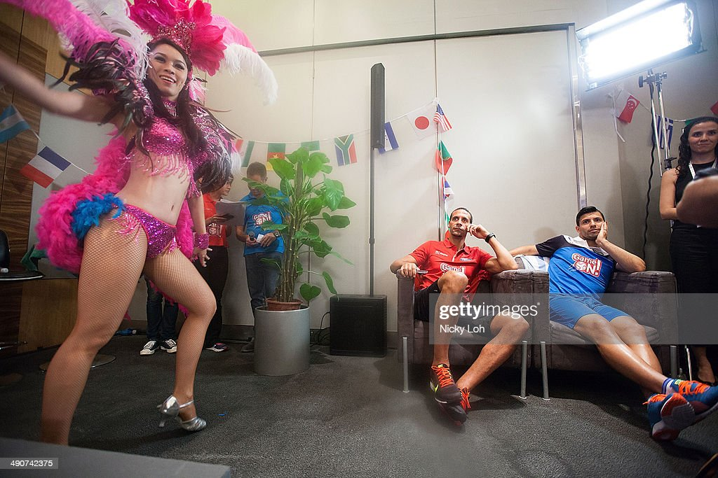 Rio Ferdinand (C) of Manchester United and Sergio Aguero (2nd R) of Manchester City watch a samba performance during a press conference on May 15, 2014 in Singapore.